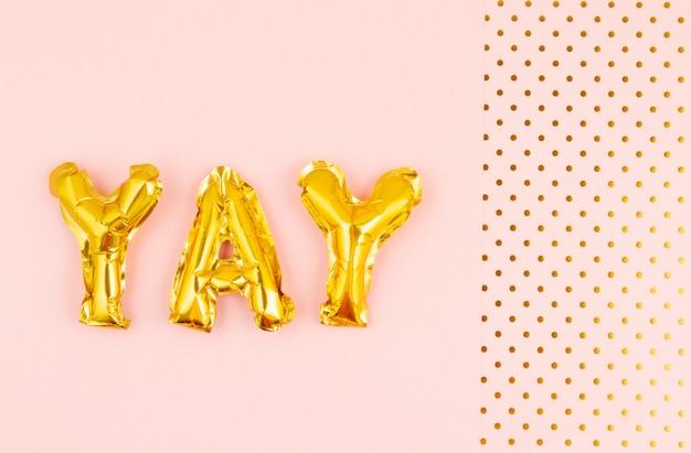 Lettere gonfiate yay ove lo sfondo pastello con pois dorati. festa, celebrazione, vacanze Foto Premium