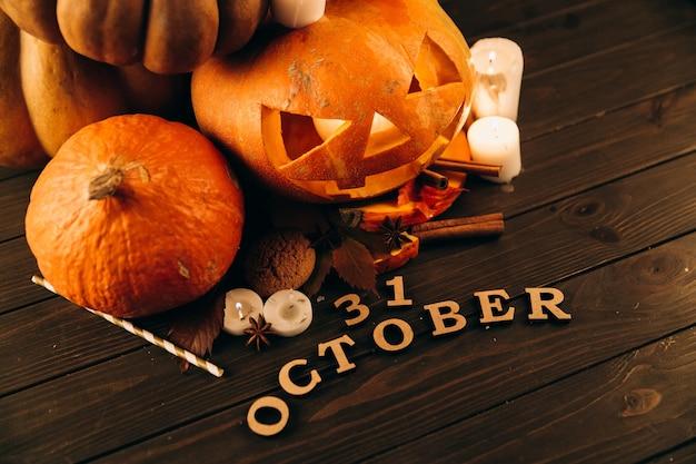 Lettere in legno '31 ottobre 'si trovano davanti a grandi zucche di hallooween, candele Foto Gratuite