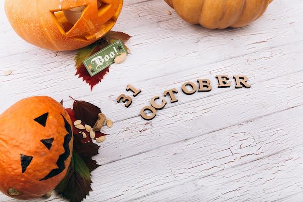 Lettere in legno '31 ottobre 'si trovano prima di grandi zucche di hallooween scarry sul tavolo bianco Foto Gratuite