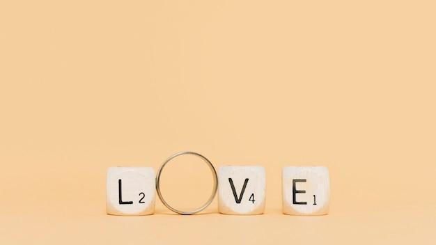 Lettere in legno e anello di fidanzamento ortografia amore sullo sfondo beige Foto Gratuite