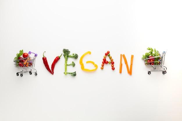 Lettering vegano fatto di verdure con piccoli carrelli della spesa Foto Gratuite