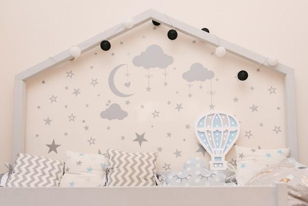Lettino per bambini bianco in legno grigio a forma di casa con stelle e luna sul muro, luce notturna in legno a forma di palloncino, arredamento camera dei bambini Foto Premium