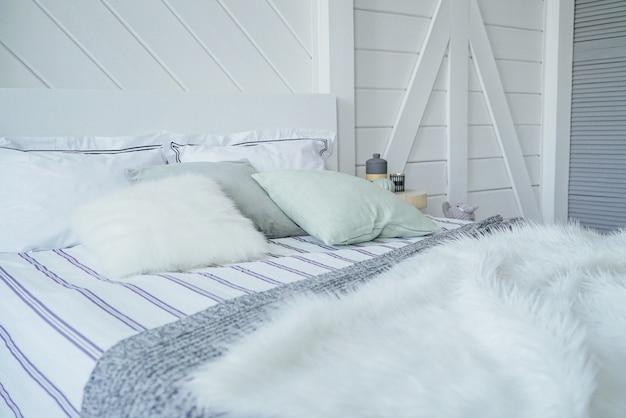 Letto con cuscini e coperta in maglia di pelliccia in interni moderni scandinavi Foto Premium