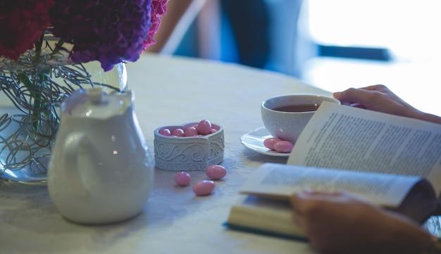 Lettura di un libro con una tazza di tè e caramelle rosa a parte Foto Gratuite