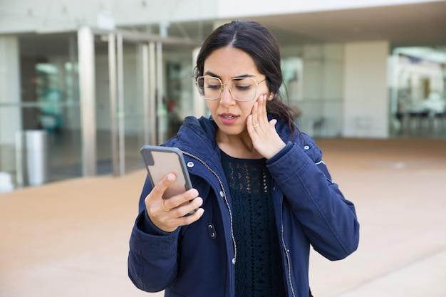 Lettura sorpresa della ragazza sullo schermo dello smartphone Foto Gratuite