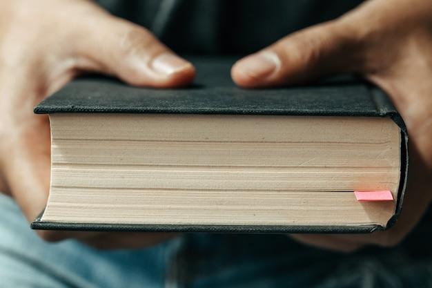 Letture della domenica, bibbia. primo piano mani uomo che tengono la bibbia Foto Premium