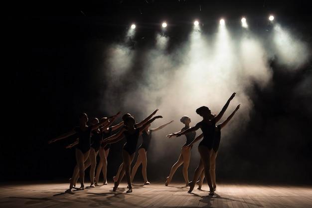 Lezione di danza classica sul palcoscenico del teatro con luci e fumo. Foto Premium