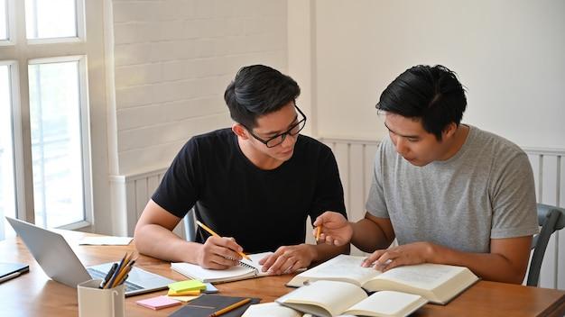 Lezione di due uomini insieme con i libri sul tavolo. Foto Premium