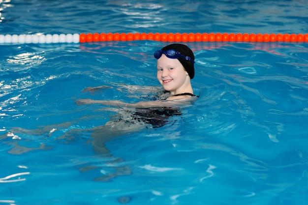 Lezioni di nuoto per bambini in piscina - una bella ragazza dalla pelle chiara nuota nell'acqua Foto Premium