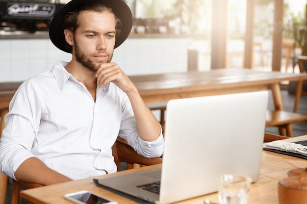 Libero professionista barbuto che si collega alla rete wireless tramite laptop. uomo premuroso che lavora sul taccuino mentre era seduto al tavolo di legno nell'interiore moderno della caffetteria. libro di lettura degli studenti al caffè Foto Gratuite