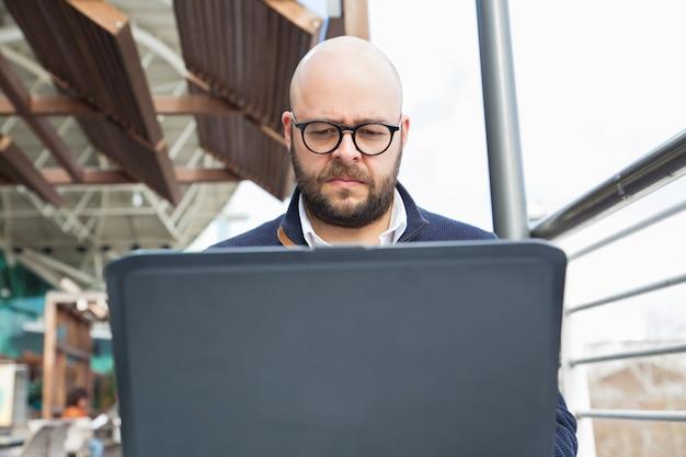 Libero professionista concentrato serio che per mezzo del computer portatile Foto Gratuite
