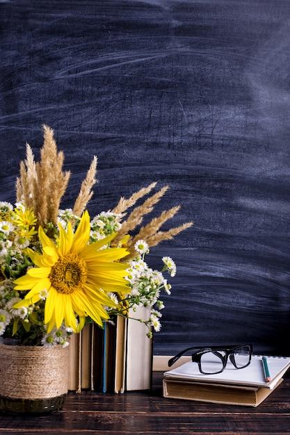 Libri, bicchieri, pennarelli e un mazzo di fiori in un vaso su bianco Foto Premium