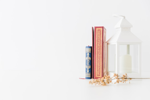 Libri del corano con lanterna e ramo Foto Gratuite