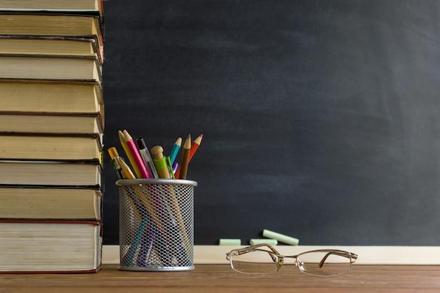 Libri dell'insegnante di vetro e un supporto con le matite sulla tavola, sui precedenti di una lavagna con gesso Foto Premium