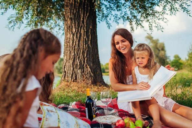 Libri di lettura dei bambini e della madre all'aperto. famiglia che ha picnic nel parco al tramonto. Foto Premium