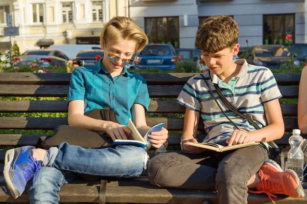 Libri di lettura sorridenti di due ragazzi di scuola che si siedono sul banco in città Foto Premium