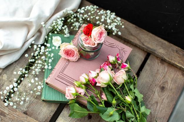 Libri di rose di una vista frontale colorati sul pavimento di legno marrone Foto Gratuite