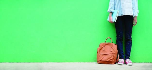 Libri e borsa di scuola della tenuta della ragazza dello studente Foto Premium