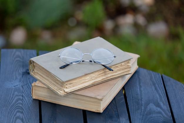 Libri e vetri d'annata sulla tavola di legno in un giardino di tempo di primavera Foto Premium