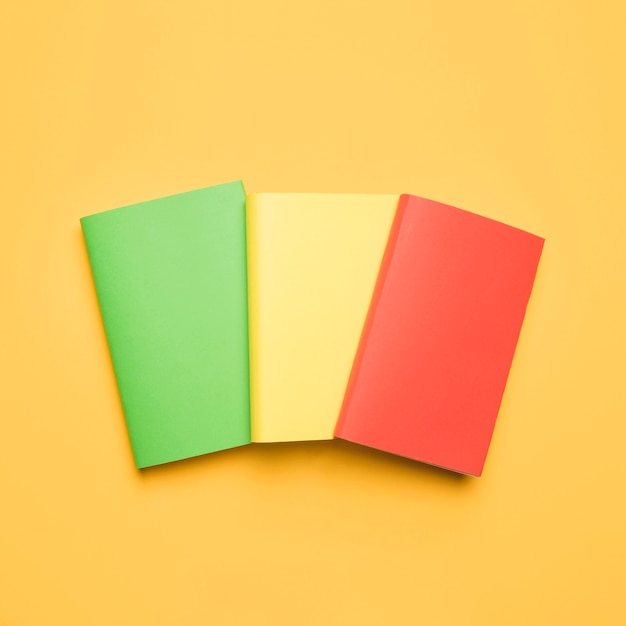 Libri in bianco variopinti su fondo giallo Foto Gratuite