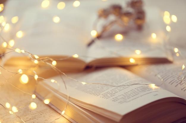 Libri invernali. lettura accogliente invernale. macro pagine e fuoco molle della ghirlanda brillante. mood accogliente. stagione invernale Foto Premium
