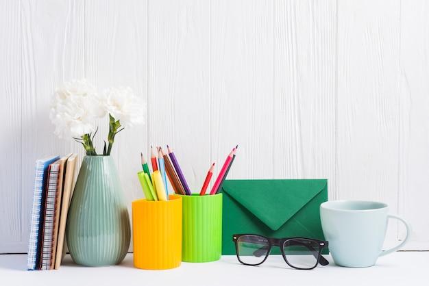 Libri; vaso; segnaposto; busta; tazza di occhiali e ceramica contro il contesto in legno Foto Gratuite