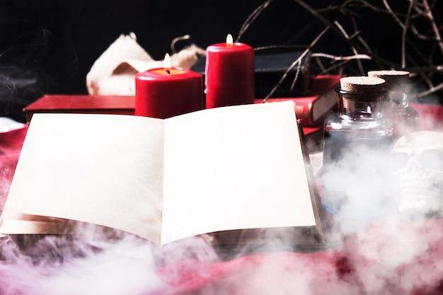 Libro aperto in fumo con attributi di halloween Foto Gratuite