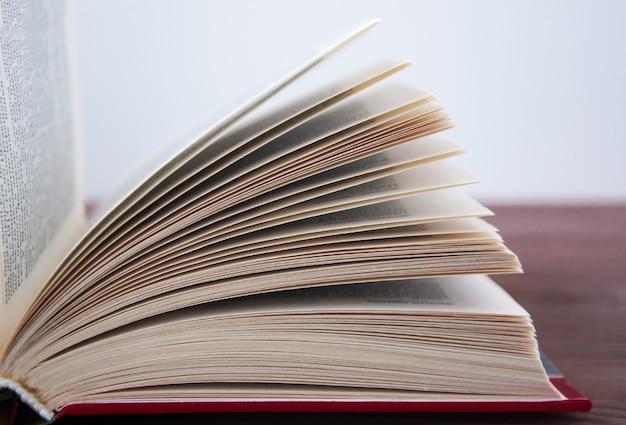 Libro aperto, sdraiato su un tavolo di legno con tonificante. Foto Premium
