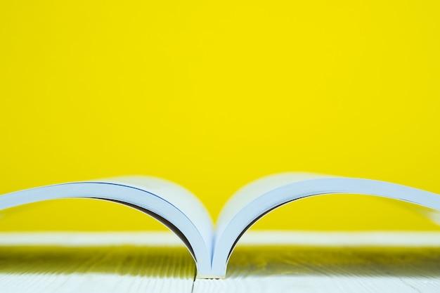 Libro aperto sul tavolo bianco con scena gialla. Foto Premium