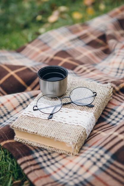 Libro, bicchieri e tè caldo di un thermos giacciono su una coperta Foto Premium