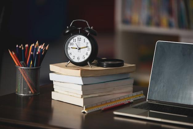 Libro, computer portatile, matita, orologio sulla tavola di legno in biblioteca, istruzione che impara concetto Foto Gratuite