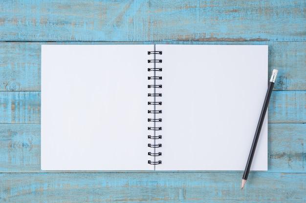 Libro dello schizzo e della matita sul tavolo in legno blu d'epoca Foto Gratuite
