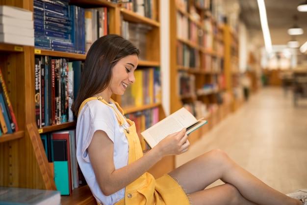 Libro di lettura allegro della giovane donna in biblioteca Foto Gratuite