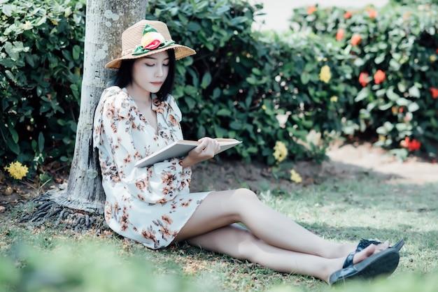 Libro di lettura bella ragazza al parco in luce sole estivo Foto Gratuite