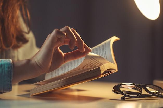 Libro di lettura della donna alla sera a casa vicino su Foto Premium
