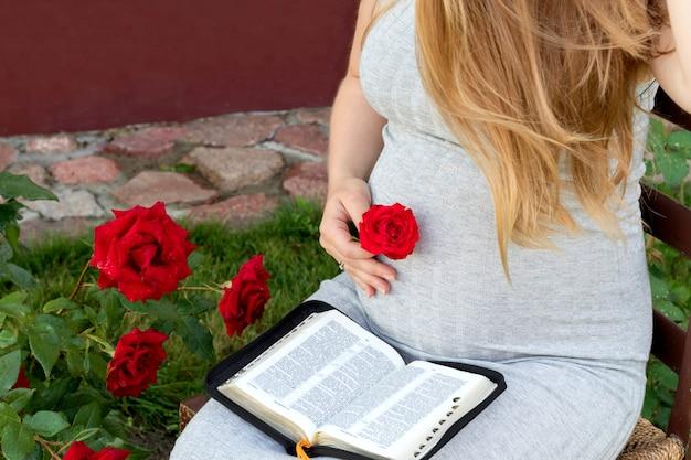 Libro di lettura della donna incinta (bibbia) in giardino. aspettando il bambino. Foto Premium