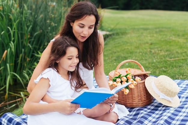 Libro di lettura della figlia e della madre al picnic Foto Gratuite