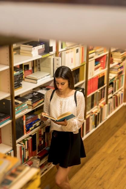 Libro di lettura della giovane signora vicino allo scaffale Foto Gratuite