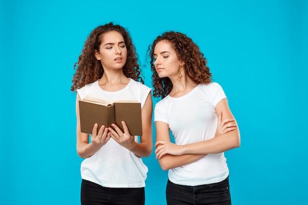 Libro di lettura di due gemelli della donna sopra il blu. Foto Gratuite