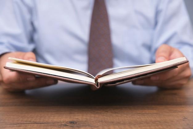 Libro di lettura di uomo d'affari sul tavolo Foto Premium