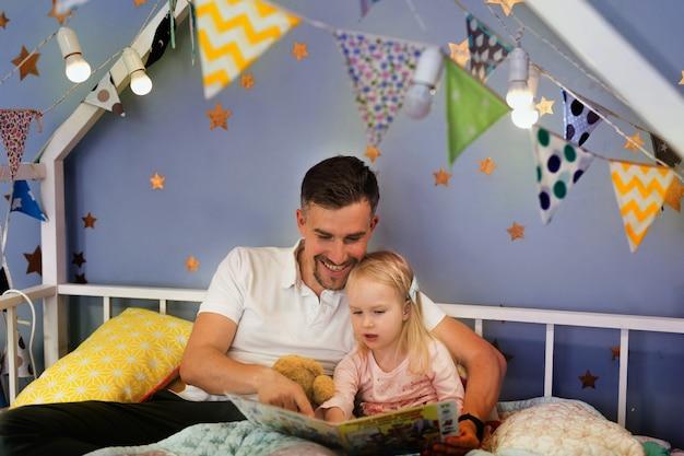 Libro di lettura felice del padre con la sua bambina mentre sedendosi sul letto prima di coricarsi insieme Foto Premium