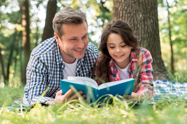 Libro di lettura felice della figlia e del padre insieme al parco Foto Gratuite