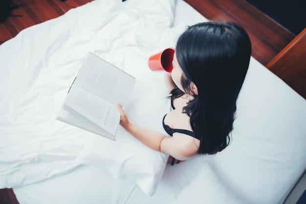 Libro di lettura sexy della donna e tazza di caffè di tenuta a letto Foto Gratuite