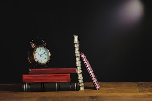 Libro di testo e sveglia di natura morta sul tavolo. Foto Premium