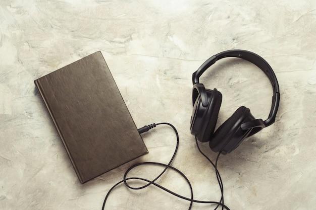 Libro e cuffie collegati ad esso su una pietra bianca Foto Premium