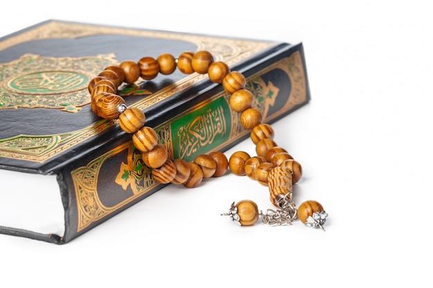 Libro islamico sacro corano e perline su sfondo bianco Foto Premium