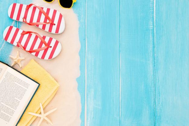 Libro, telo mare, infradito, occhiali da sole, sabbia su fondo di legno blu Foto Gratuite