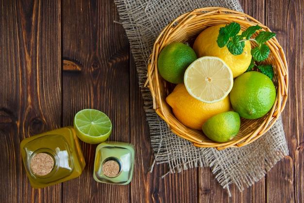 Limes con limoni, bibite, erbe in un cestino di vimini su legno e pezzo di sacco, piatto disteso. Foto Gratuite