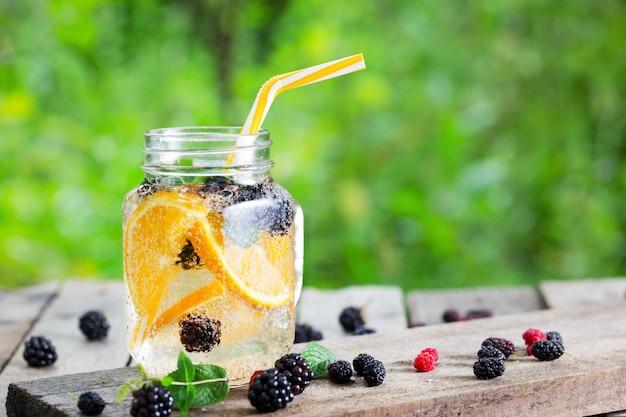 Limonata cocktail da arancia e bacche in barattolo di vetro Foto Premium