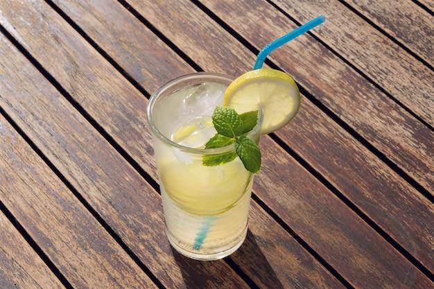 Limonata fresca in vetro con paglia su un tavolo di legno Foto Premium